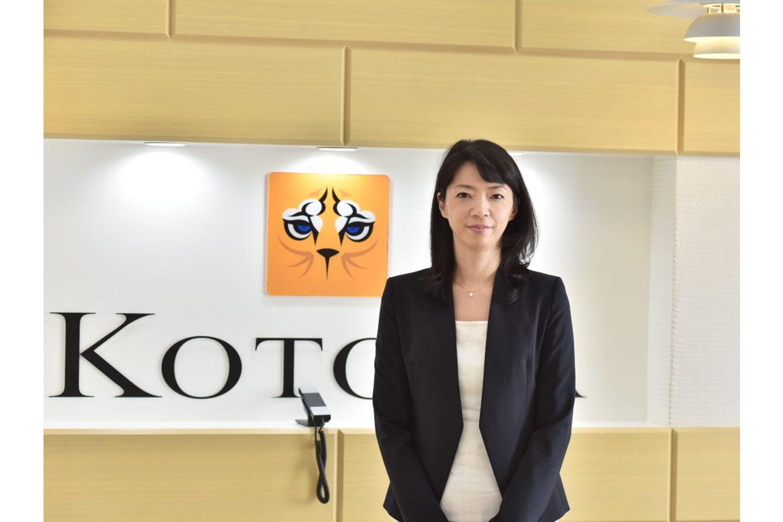 会社の看板の前で写真に写る大西利佳子さん